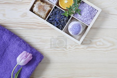 Photo pour Close-up of Ingredients for aromatherapy and spa treatments with tulip flower, aromatic sea salt and towels. Spa kit for beauty and health on white wooden background. - image libre de droit