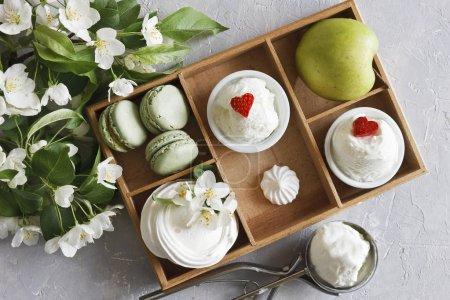 Photo pour Photo en gros plan de tasses froides de crème glacée avec macarons, pomme verte dans une boîte en bois et de belles fleurs fraîches sur fond de table gris. Vue du dessus - image libre de droit