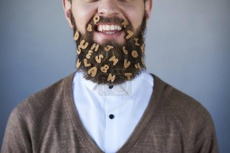smiling bearded man with letter stickers