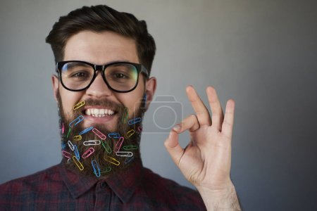Photo for Portrait of handsome man in glasses with paper clips in beard gesturing OK sign on gray background - Royalty Free Image
