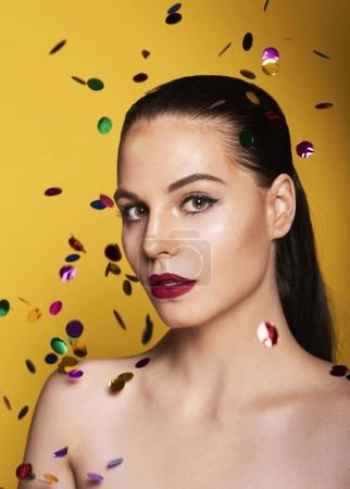 Closeup of Beauty Woman Face with confetti. Portrait Of Beautiful Young Female Model With Soft Smooth Skin And Professional Facial Makeup