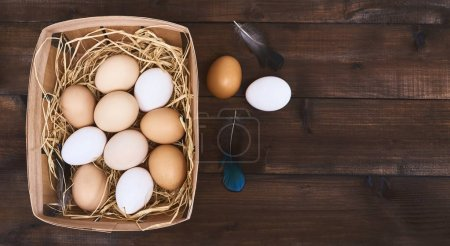 Photo for Top view of fresh chicken eggs in wooden box with hay and feathers on wooden background. - Royalty Free Image
