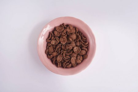 Photo for Top view of pink plate with chocolate cornflakes - Royalty Free Image