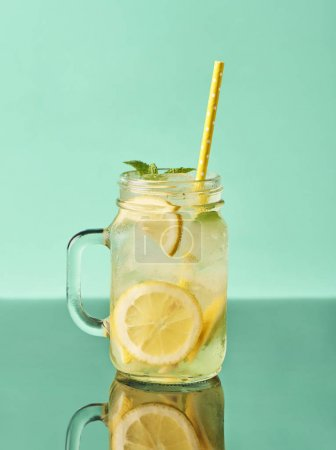 Fresh tasty lemonade in mason jar glass on turquoise background