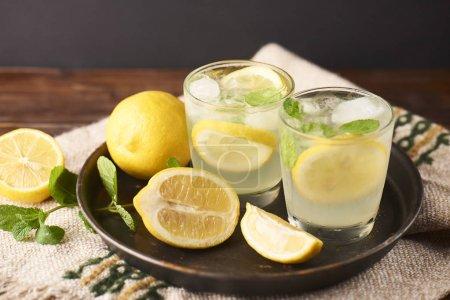 Fresh tasty lemonade in glasses on dark background.