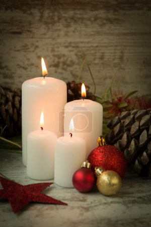 candles in a Christmas setting with seasonal decorations