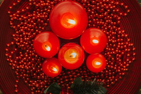 Lighted red candles with pearls