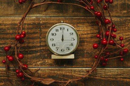 golden alarm clock with red berries