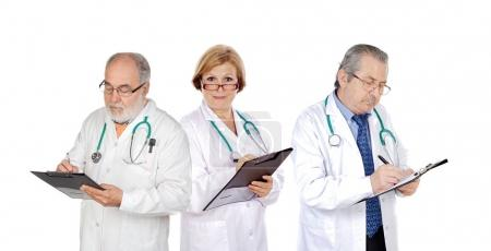 Photo for Three mature doctors filling in reports isolated on white background - Royalty Free Image