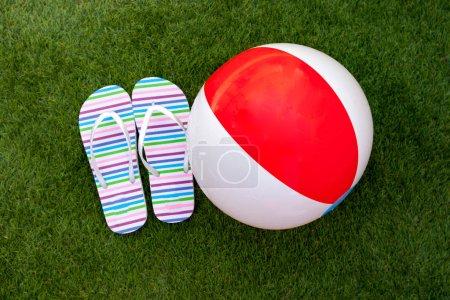 Flip-flops and ball on green grass