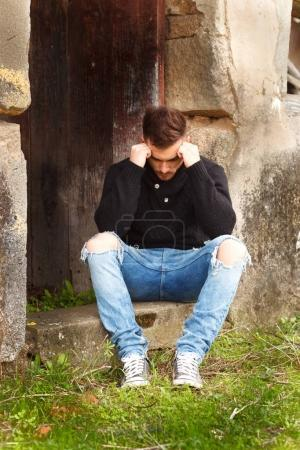 attractive guy wearing black jersey posing against old house