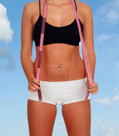 female body with tape measure in underwear and blue sky on background