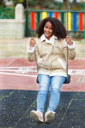 happy african girl with beautiful hair on swing in park