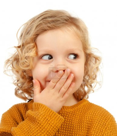 portrait of happy little child with long blond hair covering mouth isolated on white background