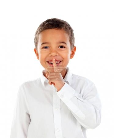 cute little African boy in white shirt with forefinger at his lips as sign of silence, isolated on white background