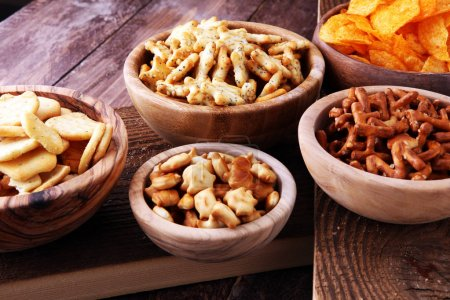Photo for Salty snacks. Pretzels, chips, crackers in wooden bowls. - Royalty Free Image