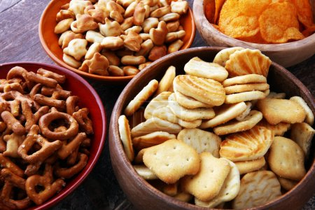 Photo for Salty snacks. Pretzels, chips, crackers in wooden bowls - Royalty Free Image