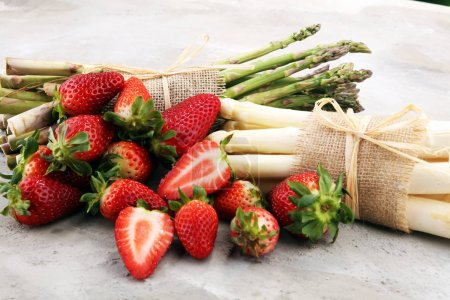 Photo pour Asperges fraîches blanches et vertes avec un bouquet de fraises saines - image libre de droit