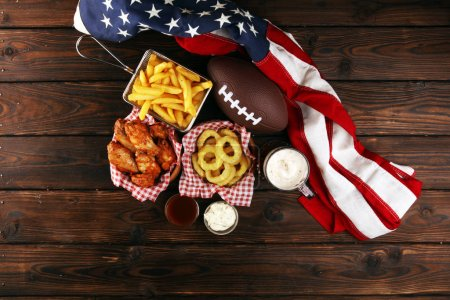 Las alas de gallina, las patatas fritas y los aros de cebolla para el fútbol sobre la mesa. Gr.