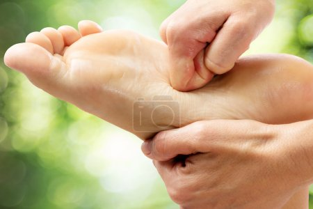 Photo for Macro close up of therapist applying pressure on foot in spa. - Royalty Free Image