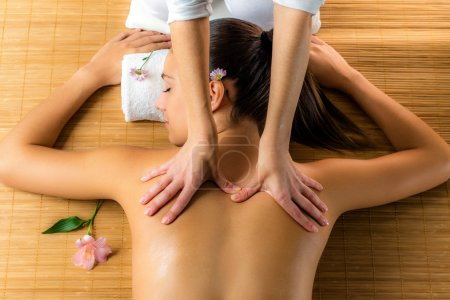 Photo for Close up top view of attractive woman enjoying healing back massage.Woman relaxing in low candle light atmosphere. - Royalty Free Image