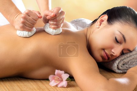 Woman enjoying aromatic pinda massage.