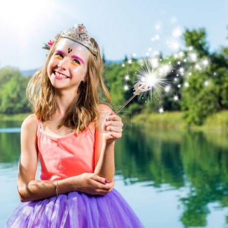 Cute girl playing with magic wand at lake.