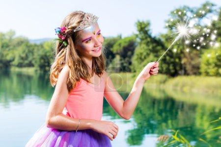 Photo pour Portrait de beauté conceptuelle de petite fille déguisée en petite princesse. Sort de casting fille avec la baguette magique à côté du lac. - image libre de droit