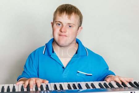 Photo for Young handicapped musician playing piano - Royalty Free Image