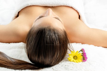 Woman laying on massage bed in spa