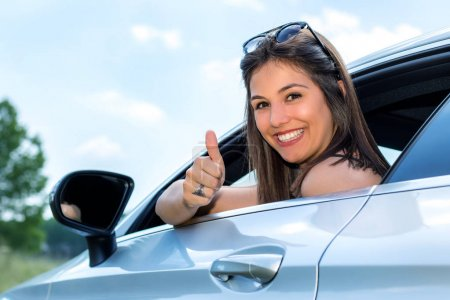 Young female car driver doing thumbs up.
