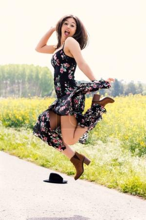 Happy girl in flower dress jumping outdoors.
