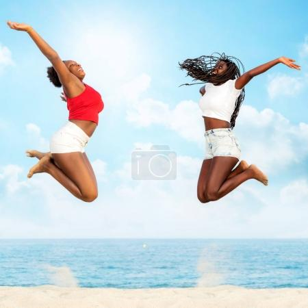 african friends jumping together on beach.