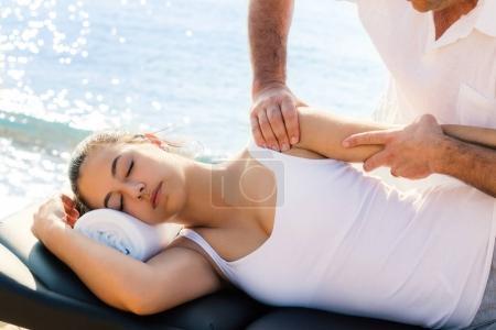 Photo pour Gros plan de sexe masculin ostéopathe fait thérapie épaule et le bras sur la jeune athlète féminine sur emplacement à côté de la mer. - image libre de droit