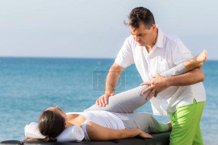 Photo pour Gros plan de sexe masculin ostéopathe faisant le traitement de la hanche et la jambe à l'extérieur sur la patiente. - image libre de droit