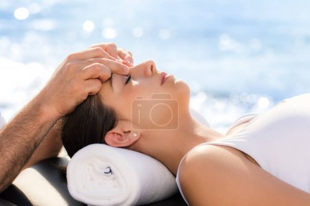 Photo pour Gros plan, Portrait de jeune femme à l'extérieur de session de traitement ostéopathique. Thérapeute en appliquant une pression entre les yeux. - image libre de droit