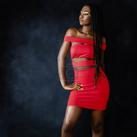 Photo for Close up portrait of sensual young african woman in red dress.Studio shot of girl  with long braided hair against fringe background. - Royalty Free Image