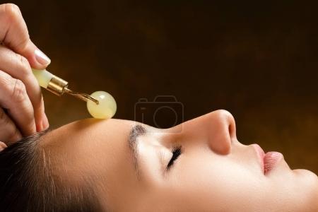 Therapist applying jade roller on forehead