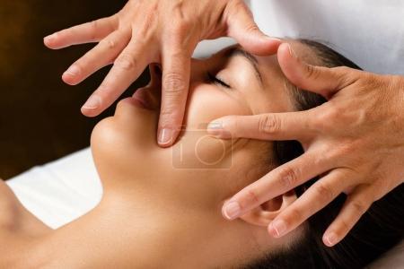 Therapist massaging female cheek.
