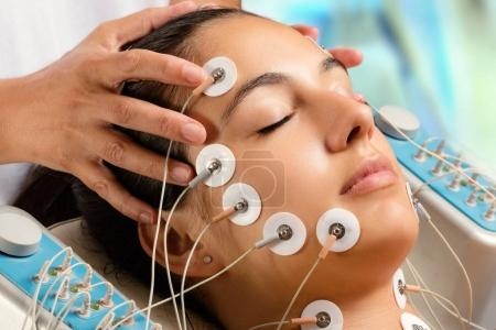 Woman having electrical facial treatment.