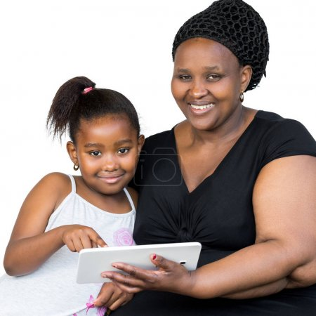 African mother with little daughter holding tablet.