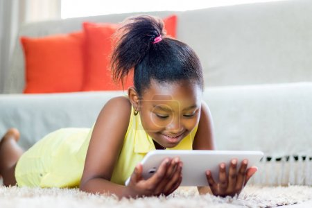 Little african girl playing on tablet in living room.
