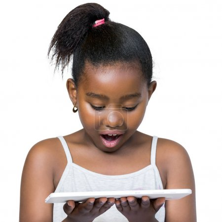 Little african girl looking at tablet with surprised facial expr