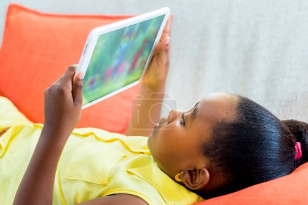 Little african girl watching cartoons at home on tablet.