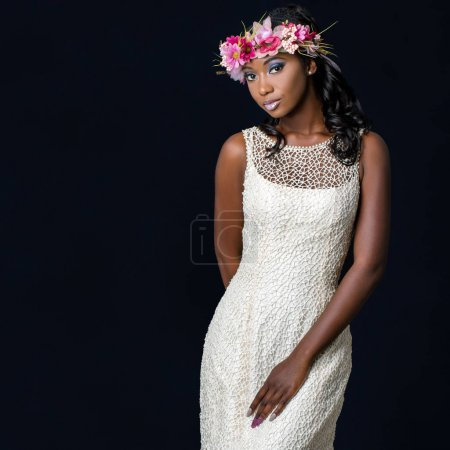 Photo for Close up studio portrait of attractive young african bride wearing white wedding gown. Medium shot of girl with colorful flower garland against dark background. - Royalty Free Image