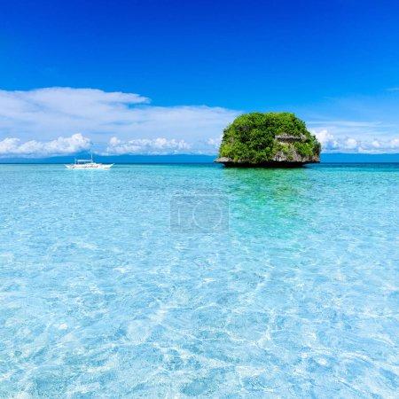 white sailboat sailing to tropical island