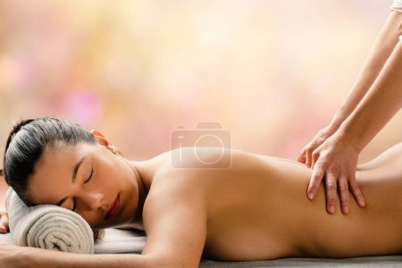 Photo for Medium side view portrait of young woman having hot aromatic oil massage is spa.Therapist applying pressure on spinal column. - Royalty Free Image