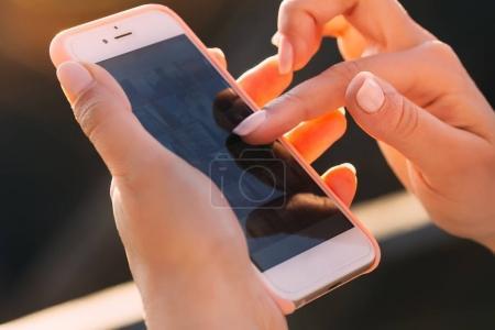 Photo pour Gros plan des doigts de la femme faisant défiler des photos sur son téléphone. Fille tenant un smartphone poste des photos dans instagram - image libre de droit