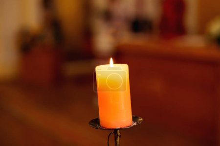Photo for One light candle burning brightly in the blurred background - Royalty Free Image