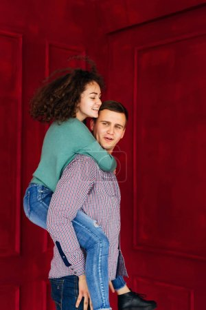 Photo pour La fille a sauté sur le dos à son petit ami sur le fond du mur rouge - image libre de droit